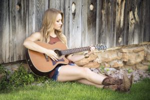 Beautiful blonde woman playing guitar 5K