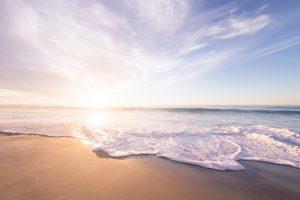 Sunrise on the horizon of a beach 4K