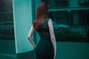 Elegant redhead woman who looks at herself in the mirror