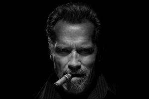 Arnold Schwarzenegger smokes a cigar in the dark