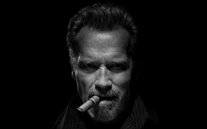 Arnold Schwarzenegger smokes a cigar in the dark