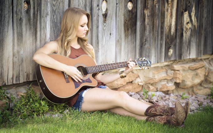 Beautiful Blonde Woman Playing Guitar