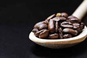 Coffee beans in a wooden spoon 4K