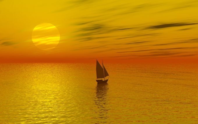 Sailboat Crossing The Sea During A Sunset