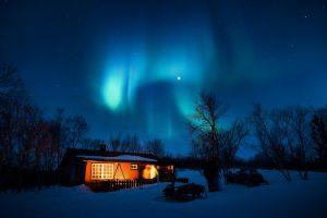 Aurora Borealis Over A Snowy House