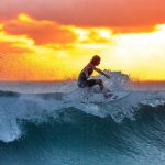 Man Surfing Waves at Sunset