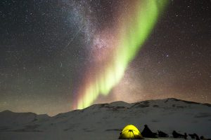 Aurora Borealis And Milky Way Above A Camp In The Snow