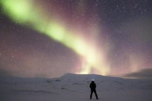 Man looking at Aurora Borealis with a Starry Sky 5K